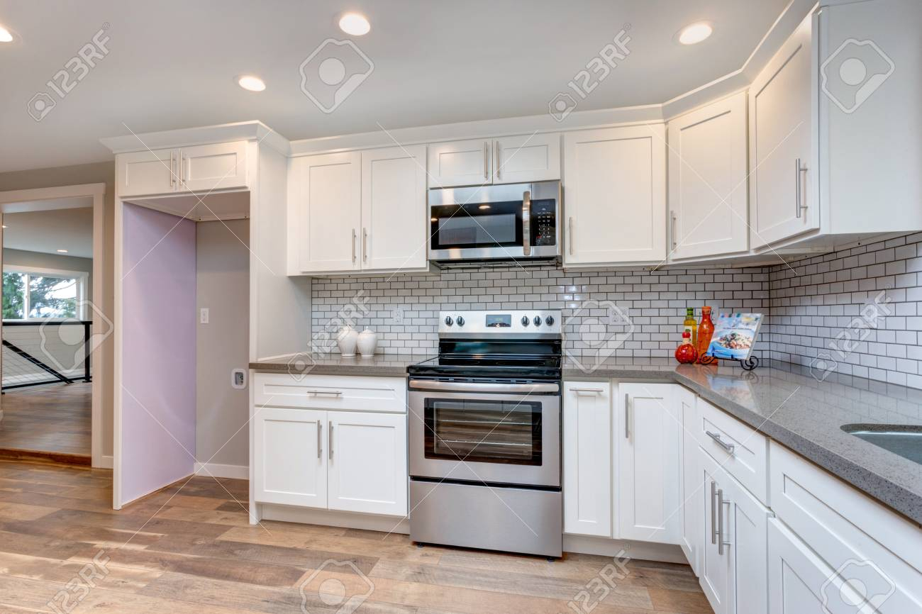 Open Concept Kitchen With White Cabinets Grey Quartz Countertops within proportions 1300 X 866
